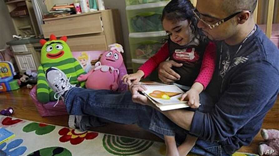 Christopher Astacio reads with his daughter Cristina, 2, who was recently diagnosed with a mild form of autism, New York, March 28, 2012.