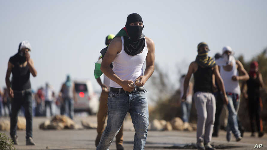 Palestinian demonstrators throw stones toward Israeli security forces during clashes after the funeral of Palestinian Saed Dawabsheh who died after an arson attack on his family's home, in the West Bank village of Duma near Nablus, Aug. 8, 2015.