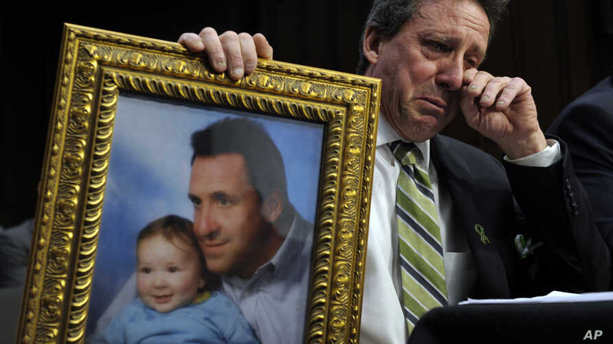 Neil Heslin, the father of a six-year-old boy who was slain in the Sandy Hook massacre in Newtown, Connecticut, on Dec. 14, 2012, holds a picture of himself with his son Jesse and wipes his eye while testifying on Capitol Hill in Washington, Feb. 27,