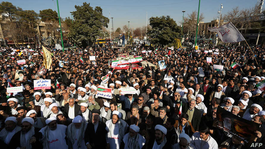 Pro-government demonstrators hold banners during a march in the central Iranian city of Isfahan, Jan. 4, 2018.