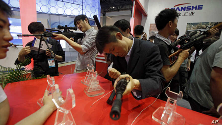 FILE - Visitors try out modern weapons during an exhibition of police equipment and anti-terror technologies held in Beijing.