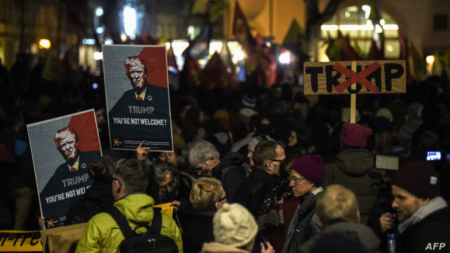 FILE - People hold up banners with images of U.S. President Donald Trump as they rally against his attendance of the Davos World Economic Forum, in central Zurich, Switzerland, Jan. 23, 2018.