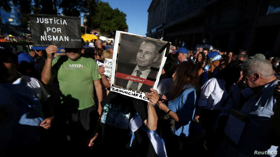 A woman holds up a photo of late state prosecutor Alberto Nisman, lead investigator into the car bomb attack that killed 85 people at a Buenos Aires' Jewish community center, during commemorations of the second anniversary of his death, in Buenos Air