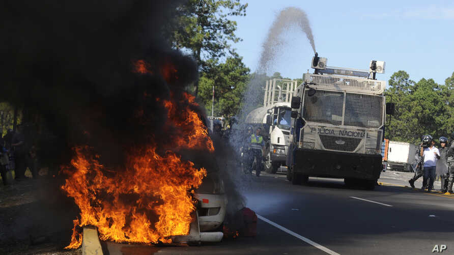 A police truck extinguishes a burning highway maintenance vehicle, after police dispersed protesters blocking a toll road and encouraging drivers not to pay, in Zambrano, north of Tegucigalpa, Honduras,  Oct. 3, 2016. Groups organized by opposition p
