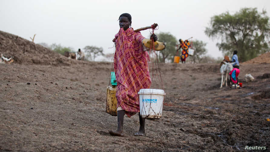 A woman carries water from a water hole near Jamam refugee camp in South Sudan's Upper Nile State, March 10, 2012.