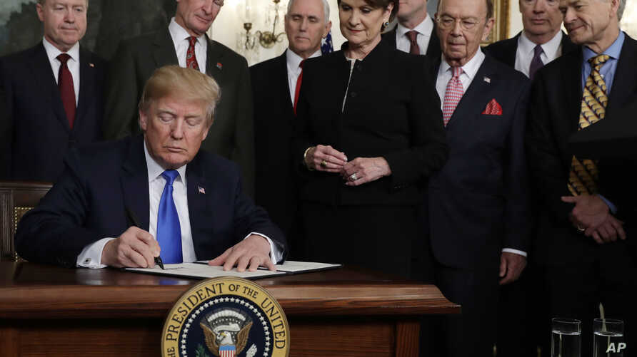 President Donald Trump signs a presidential memorandum imposing tariffs and investment restrictions on China in the Diplomatic Reception Room of the White House, March 22, 2018, in Washington.