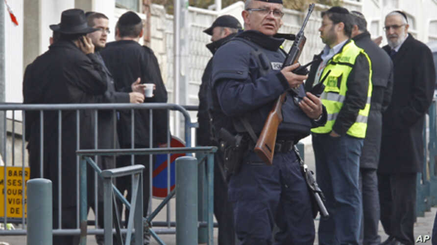 An armed police officer stands guard at the entrance of the Ozar Hatorah Jewish school in Toulouse, southwestern France, March 20, 2012.