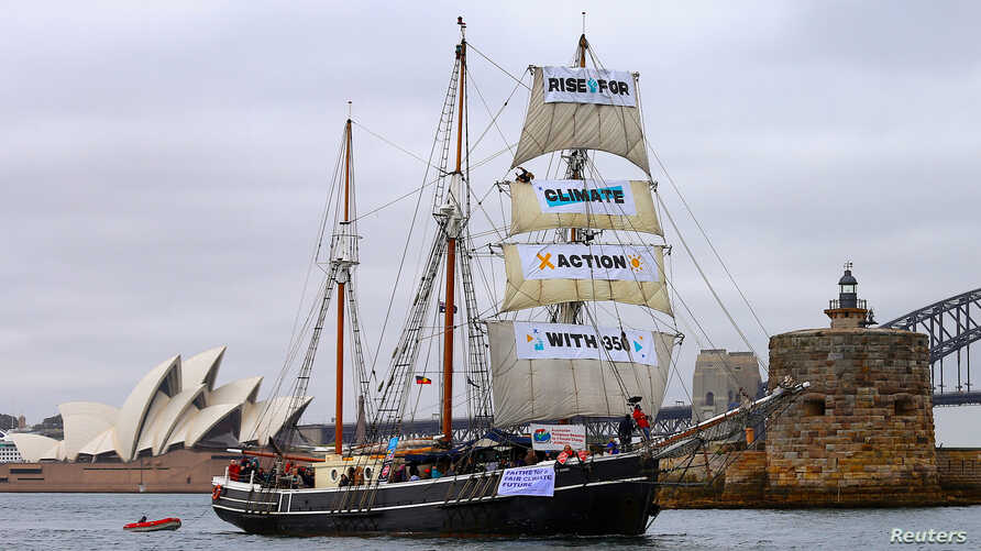 A supplied photo shows a tall ship displaying banners as it sails on Sydney Harbor in Australia, Sept. 8, 2018 as part of global climate change protests across 95 countries organized by the New York-based lobby group 350.org.