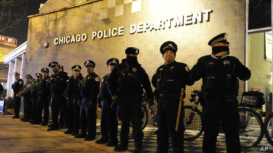 FILE - Chicago police officers line up outside the District 1 central headquarters during a protest of the police shooting of 17-year-old Laquan McDonald, in Chicago, Nov. 24, 2015.