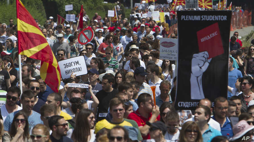 """Protesters holding a Macedonian flags and banners reading """"Resignation"""" and """"Goodbye Nikola"""" protest against Prime Minister Nikola Gruevski as they march towards the offices of Macedonia's conservative government, in capital Skopje, May 17, 2015."""
