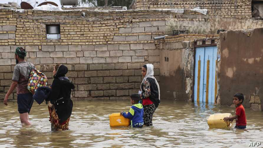 FILE - An Iranian family walks through a flooded street in a village around the city of Ahvaz, in Iran's Khuzestan province, March 31, 2019.