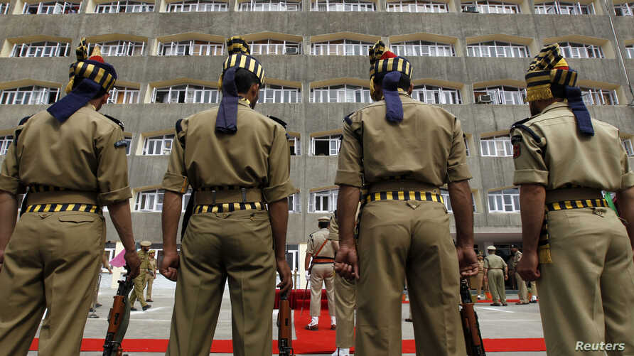 FILE - Indian policemen in ceremonial uniforms stand at attention in front of the civil secretariat complex on the first day of the Darbar Move in Srinagar, May 9, 2011.
