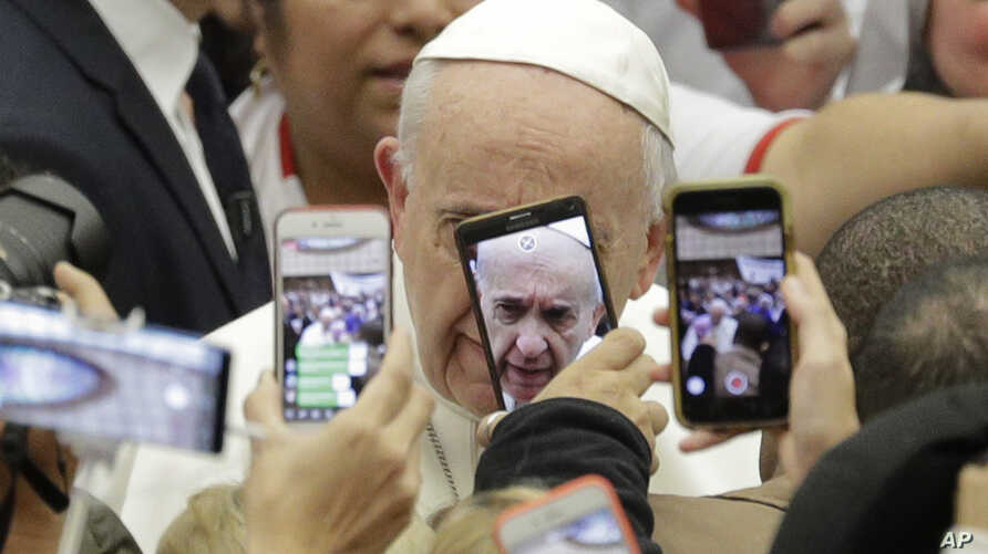 Pope Francis is framed by cellphones as he arrives for his weekly general audience, in the Pope Paul VI hall, at the Vatican, Wednesday, Jan. 9, 2019.