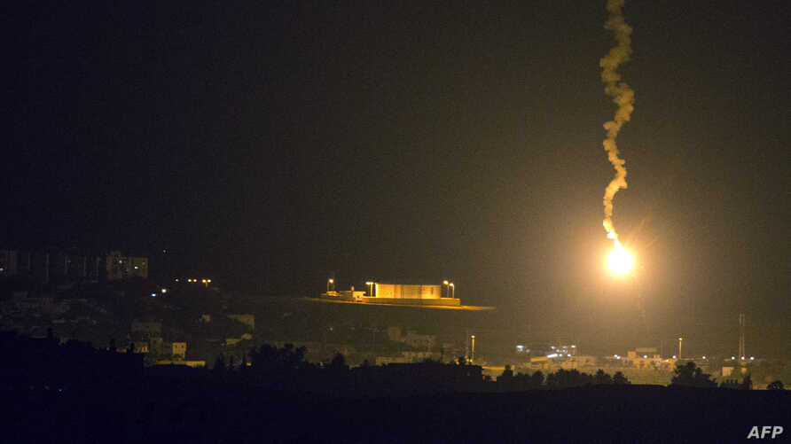 A picture taken from the southern Israeli border with the Gaza Strip shows Israeli flares illuminating the Palestinian coastal enclave, July 7, 2014.
