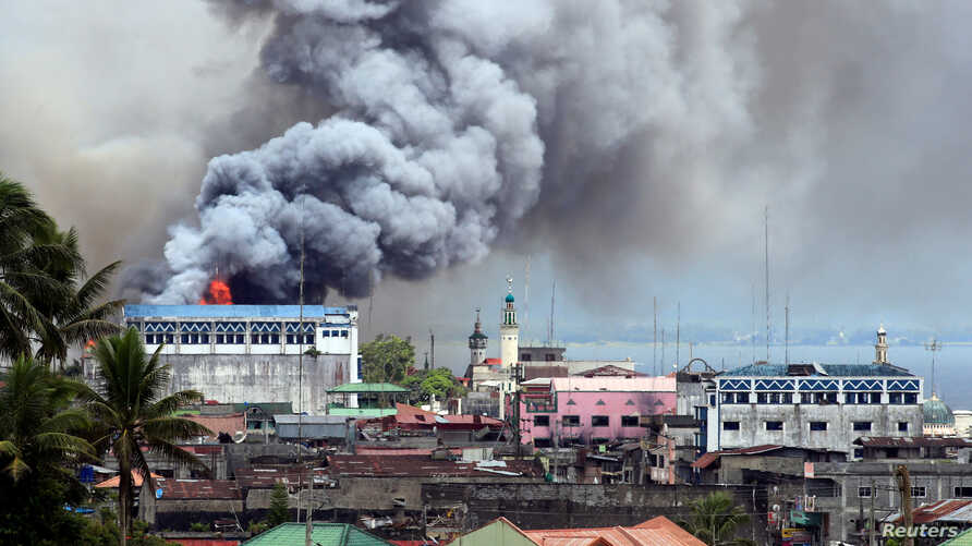 Black smoke comes from a burning building in a commercial area of Osmena street in Marawi city, Philippines June 14, 2017.