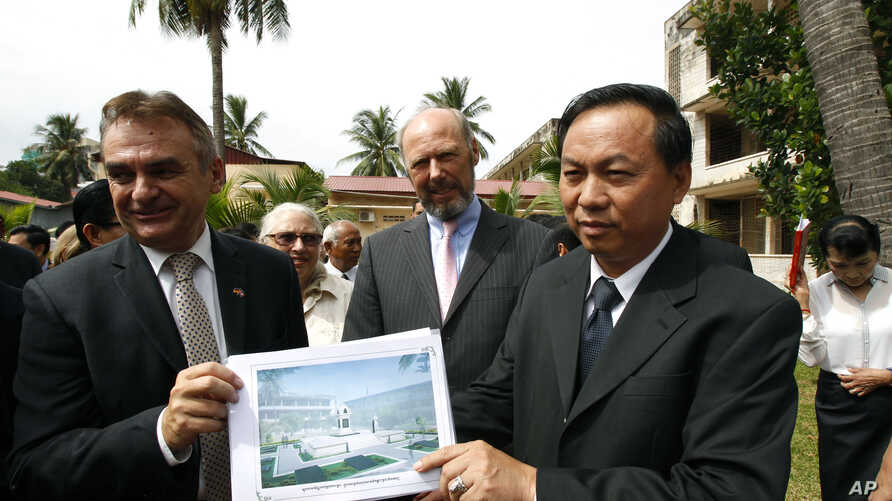 Cambodian official Han Touch (r) and German Embassy officer Adelbert Eberhardt hold a design of a memorial building as Joachim Baron Von Marschall, center, German Ambassador to Cambodia, watches at the building site, at the Tuol Sleng Genocide Museum