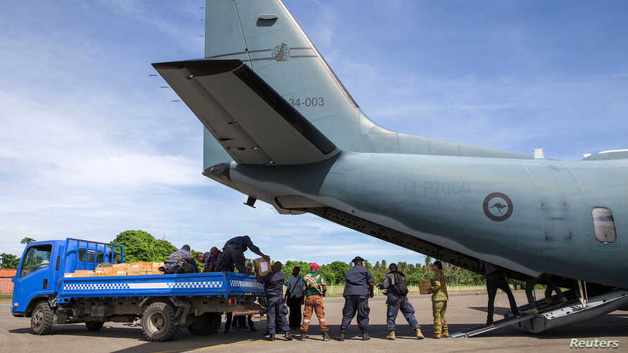 A supplied image of Australian Defence Force and Papua New Guinea Police Force personnel unloading ballot papers for the upcoming National Election, which runs from June 24 until July 8, from a C-27J Spartan aircraft in Papua New Guinea, June 15, 201