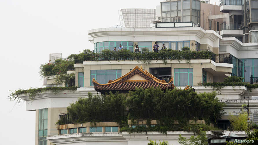 A privately-built illegal temple-like structure is seen on the top of a 20-storey residential block in the southern Chinese city of Shenzhen, August 22, 2013.