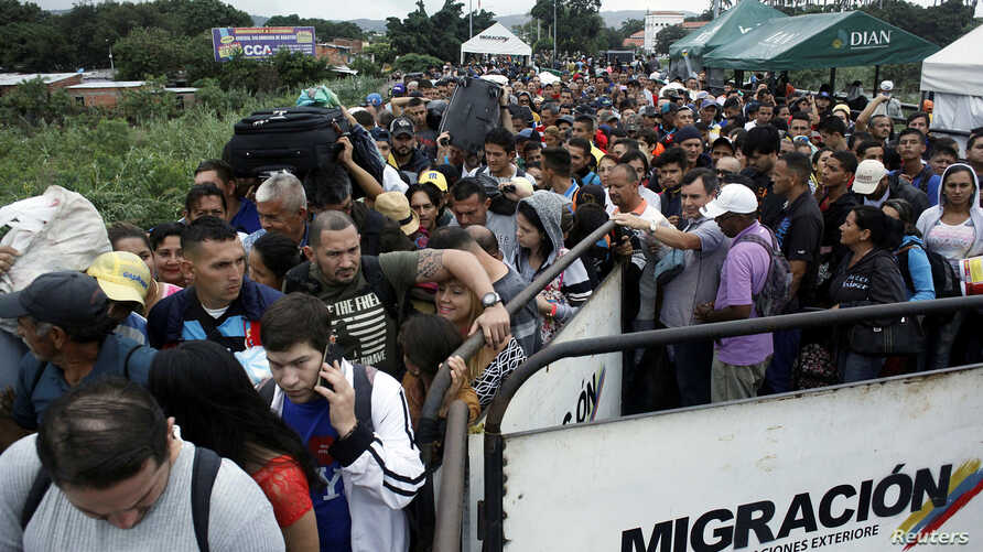 People queue to try to cross into Venezuela from Colombia through the Simon Bolivar international bridge in Cucuta, Colombia, Feb. 13, 2018.