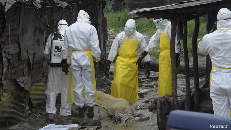 ATTENTION EDITORS - VISUAL COVERAGE OF SCENES OF INJURY OR DEATHHealth workers wearing protective clothing prepare to carry an abandoned dead body presenting with Ebola symptoms at Duwala market in Monrovia August 17, 2014.  To try to control the Ebo
