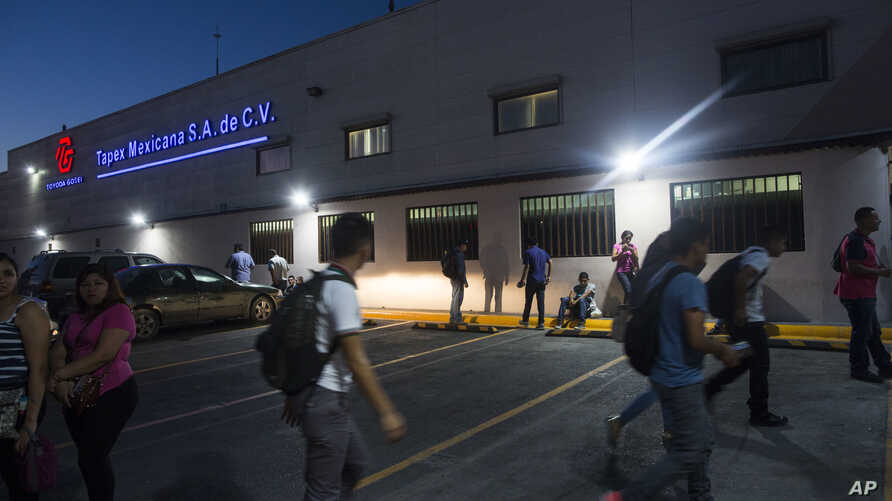 """FILE - Workers gather outside a """"maquiladora"""" for car accessories in Matamoros, Mexico, March 21, 2017. A strike at 48 plants in Matamoros is heading for victory, bringing pay raises for laborers who make less than $1 an hour assembling auto componen"""