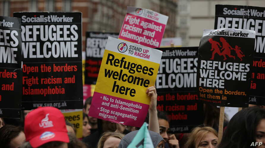 Pro-refugee activists rally with placards outside the French Embassy in central London after an aid convoy headed to northern France was turned back at the port of Dover, June 18, 2016.