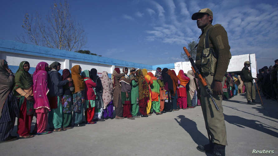 Voters line up to cast their votes as an Indian security officer stands guard outside a polling station during the last phase of the Jammu and Kashmir state assembly elections on the outskirts of Jammu, Dec. 20, 2014.