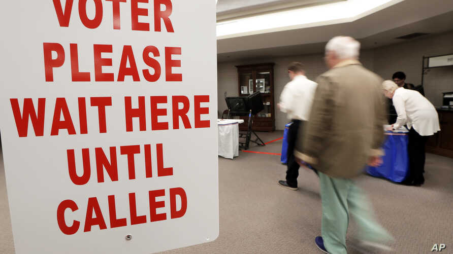A voter is escorted to a voting machine on Election Day  Nov. 8, 2016, in Nashville, Tennessee.