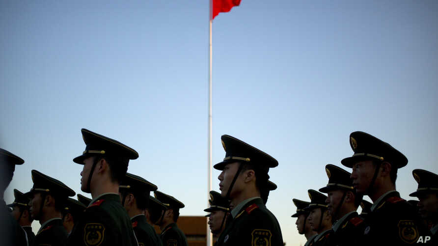 FILE - Chinese paramilitary police stand in formation after a flag raising ceremony at Tiananmen Square on National Day. Methods of torture outlined by Amnesty include beatings, sleep deprivation, being forced into painful positions for long periods,