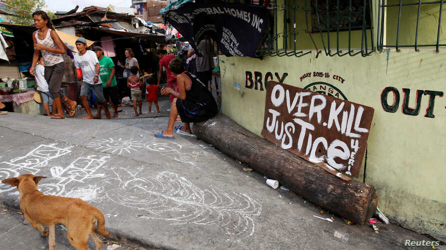 """A sign reading """"Overkill Justice for Eric"""" is displayed at the entrance of a street where Eric Quintinita Sison was killed in Pasay city, Metro Manila in the Philippines, Aug. 29, 2016. Family members of Sison said he was attempting to surrender when"""