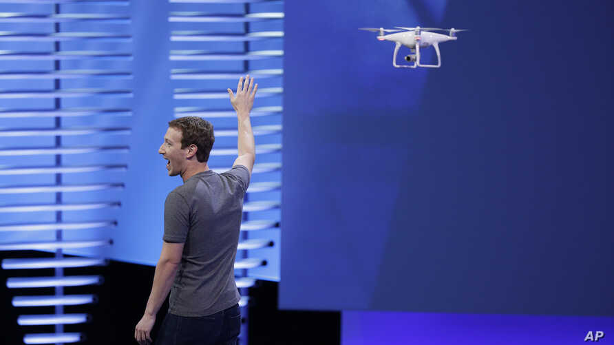 Facebook CEO Mark Zuckerberg points to a drone during his address at the F8 Facebook Developer Conference in San Francisco, April 12, 2016. Facebook said it had completed, in June 2016, a successful test flight of a drone that it hopes will help it e