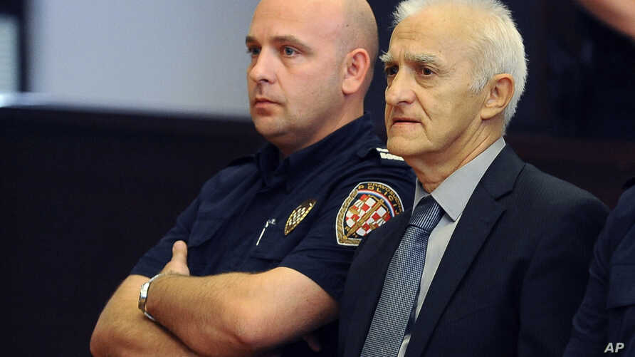 Dragan Vasiljkovic, right, a former Serb military commander sits between guards in a courtroom at the beginning of his trial in Split, Croatia, Sept. 20, 2016.