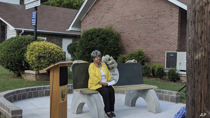 Elizabeth Eckford, one of the nine black students who first integrated Little Rock's Central High School in 1957, sits on a reconstructed commemorative bench, Sept. 4, 2018.