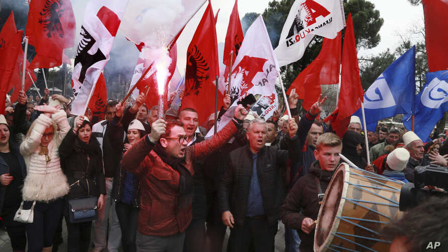 Supporters of the Albanian main opposition Democratic Party chant slogans during a protest in front of the government building in Tirana, Albania, Feb. 18, 2017.