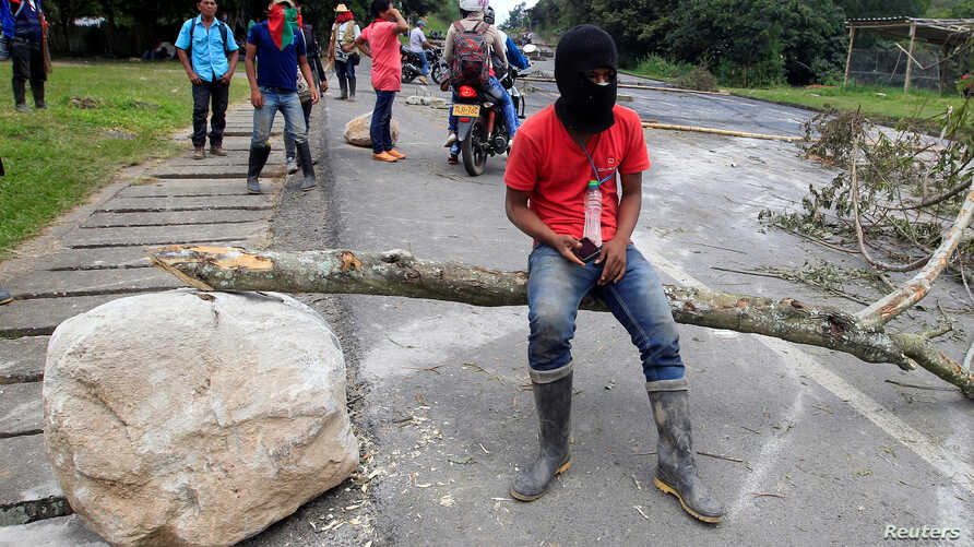 FILE - Indigenous people protest against the goverment, demanding land reform and increased state spending in rural areas, at the Panamerican highway in Mondomo, Cauca, Colombia, June 3, 2016.