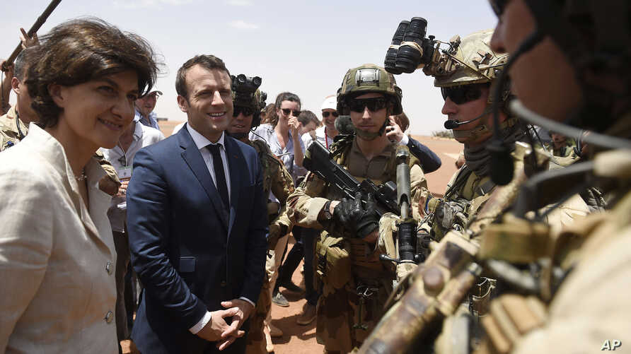 French President Emmanuel Macron, center, and Defense Minister Sylvie Goulard meet soldiers of Operation Barkhane, France's largest overseas military operation, in Gao, northern Mali, May 19, 2017.