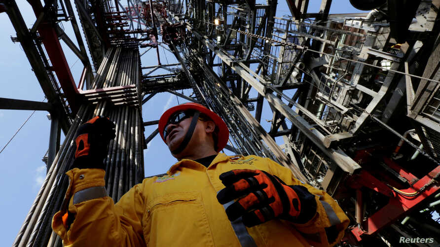 FILE - An employee works at the Centenario deep-water oil platform in the Gulf of Mexico off the coast of Veracruz, Mexico, Jan. 17, 2014.
