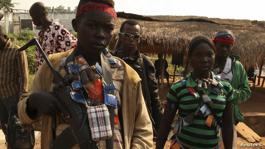 FILE - An anti-balaka child soldier wears lucky charms around his neck in the Ouengo district of Bangui, Central African Republic, Jan. 12, 2014.