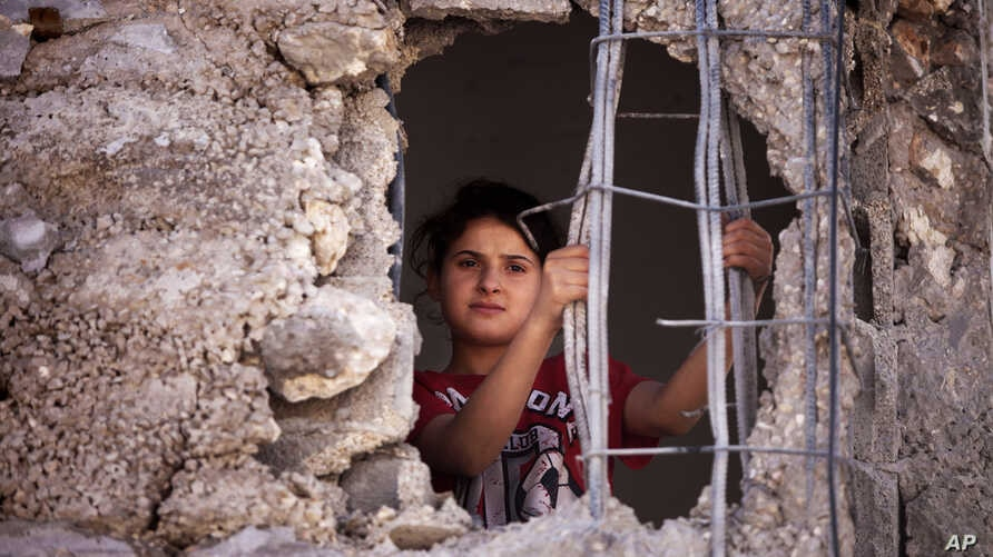 FILE - A Palestinian child looks out from the damaged family home.