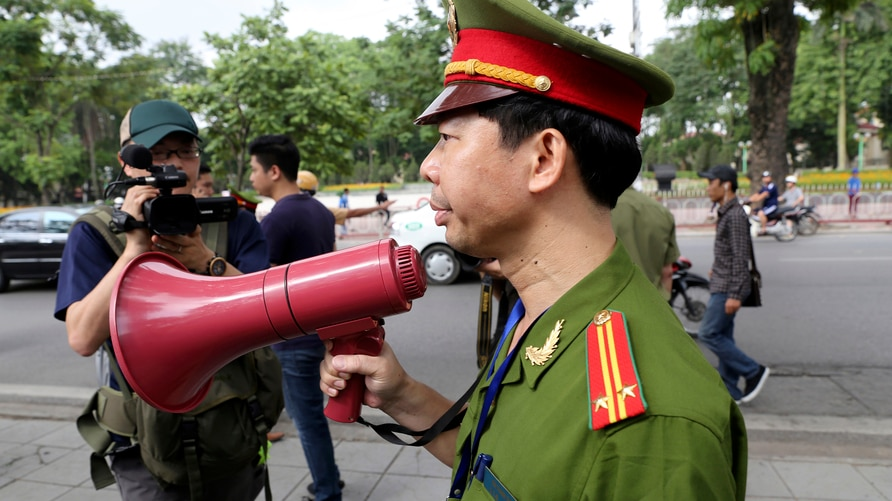 A Vietnamese police officer uses a speaker to order pedestrians including journalists to leave a closed area near the Chinese Embassy in Hanoi, Vietnam on Sunday, May 18, 2014. Vietnamese authorities forcibly broke up small protests against China in