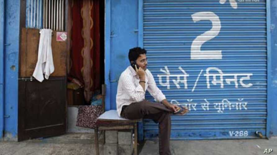 A man speaks on a mobile phone in front of shop displaying an advertisement for Uninor in Mumbai, India, February 6, 2012. Norway's Telenor plans to fight an order by India's Supreme Court to cancel 22 telecoms licences held by its Indian joint ventu