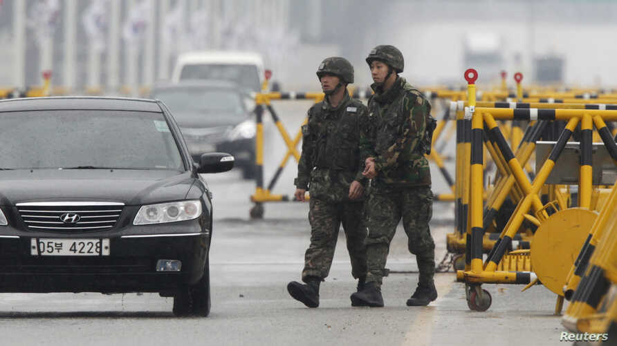 South Korean soldiers patrol as vehicles returning from North Korea's inter-Korean Kaesong Industrial Complex back to South Korea arrive at a checkpoint on the Grand Unification Bridge, which leads to the demilitarized zone separating North Korea fro