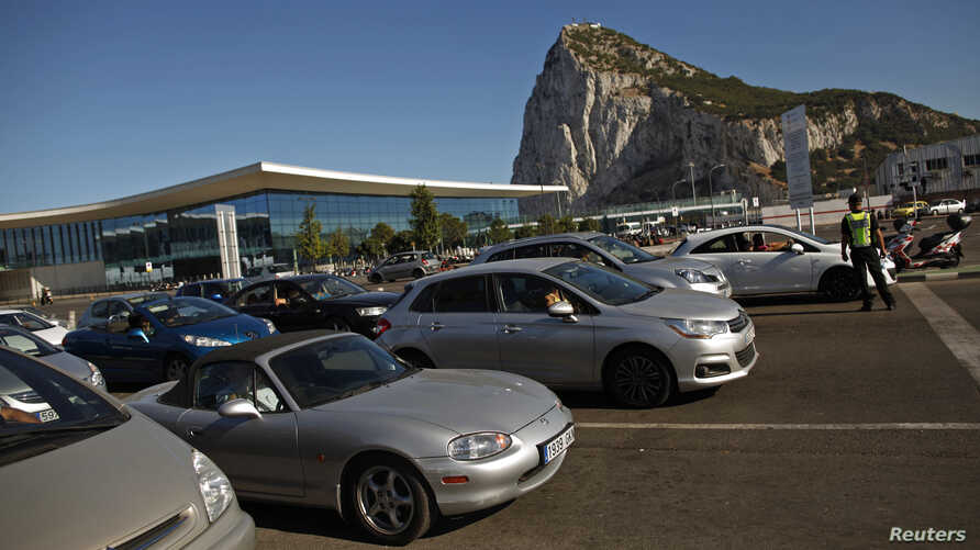 A Gibraltarian police officer guides drivers as they wait in line to enter Spain at its border with the British colony of Gibraltar in Gibraltar, July 29, 2013.