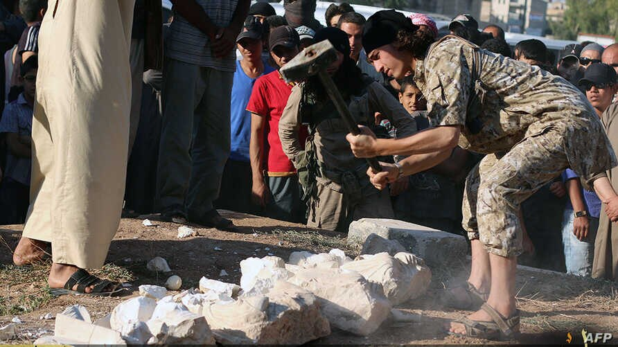An image made available by propaganda Islamist media outlet Welayat Halab on July 2, 2015 allegedly shows an Islamic State (IS) group fighter destroying ancient artifacts smuggled from the Syrian city of Palmyra, a 2,000-year-old metropolis and an Un
