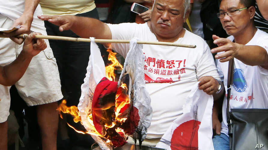 Anti-Japan protesters burn Japanese flags outside the Japanese Consulate General in Hong Kong, Sept. 16, 2012.