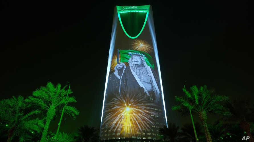 FILE - In this photo taken Sept. 24, 2017, and released by the Saudi Culture and Information Ministry, an image of King Salman and Crown Prince Mohammed bin Salman are projected on the Kingdom Tower in Riyadh, Saudi Arabia.