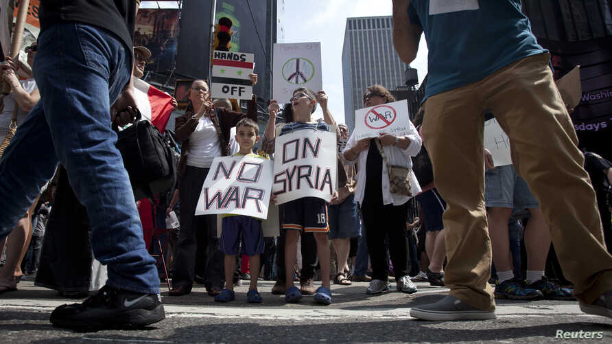 People protest against any U.S. military action against Syria, in New York City's Times Square August 31, 2013.