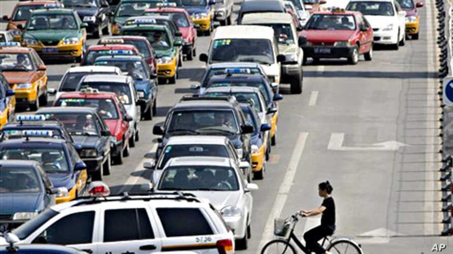 A lone Chinese cyclist faces traffic dominated by automobiles in Beijing, China (file photo)