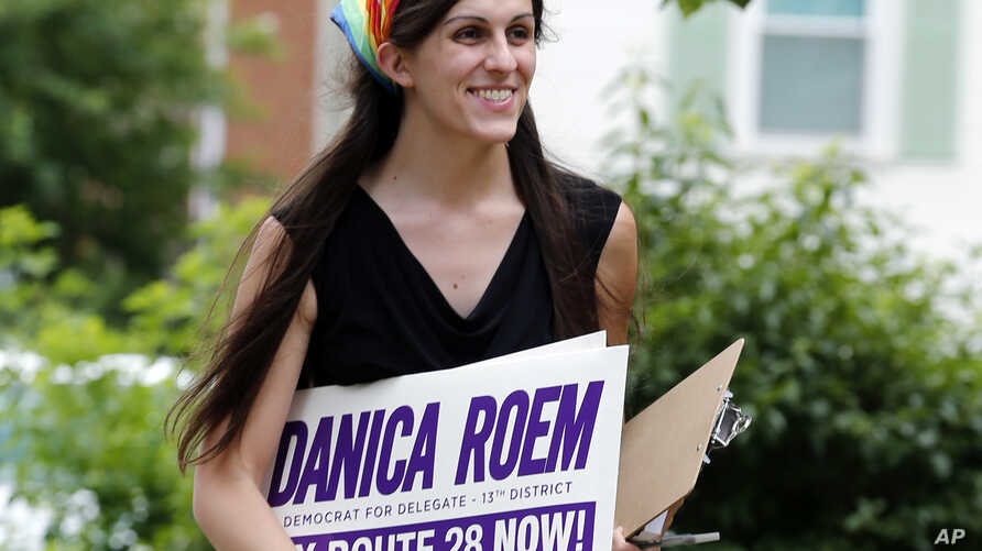 FILE - Danica Roem, then the Democratic nominee for the House of Delegates 13th district seat, holds campaign signs as she canvasses in Manassas, Va., June 21, 2017. Roem became the first openly transgender woman elected to a state legislature when s