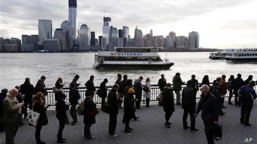A long line forms at the ferry terminal in Jersey City, N.J., as people commute toward New York City, November 5, 2012. Flooding caused by Superstorm Sandy halted mass transportation in the northern New Jersey region, with train service to New York c
